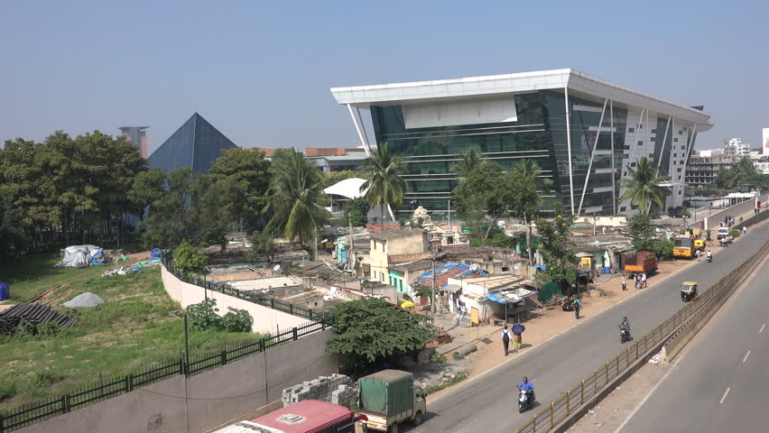 BANGALORE, INDIA - 19 NOVEMBER 2014: A brand new office tower of Infosys stands next to old slum houses, providing for an interesting contrast, in India's IT hub Bangalore.