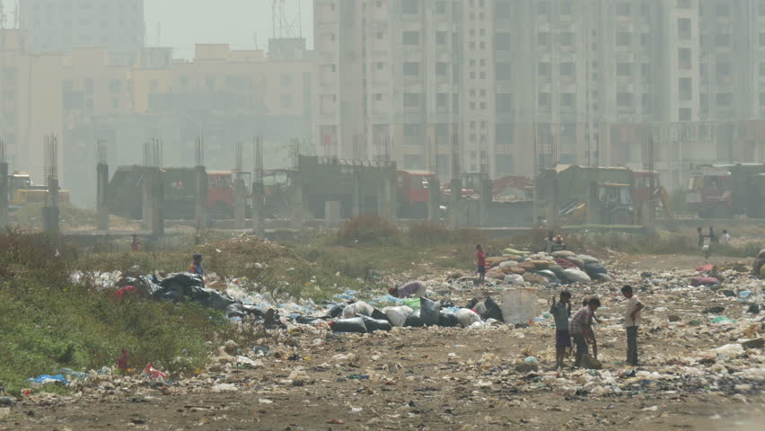 MUMBAI, INDIA - 9 NOVEMBER 2014: Unidentified people work at the Deonar garbage dump, as garbage trucks drive on and off, in Mumbai.