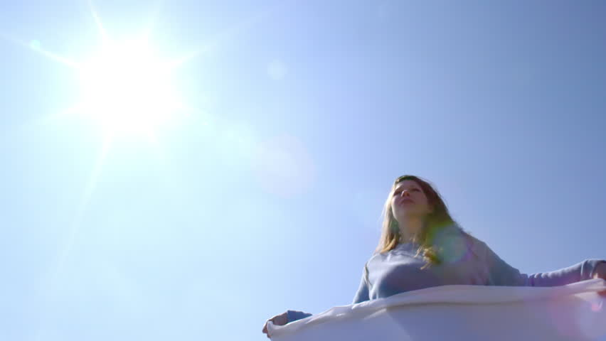 Medium shot of attractive brunette in a powder blue sweater, flipping out a clean white sheet on a sunny day.  Low angle with sun and lens flare, looking up at sky.  Slow motion, recorded at 180fps.