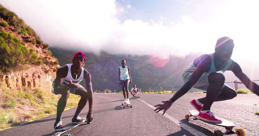 Mixed group of teenaged longboarders racing each other downhill on a mountain road in Slow Motion | Shutterstock HD Video #9517112