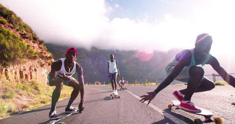 Mixed group of teenaged longboarders racing each other downhill on a mountain road in Slow Motion