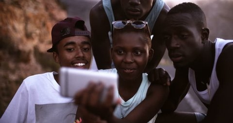 Smiling teenage African American girl taking a selfie of her friends and herself