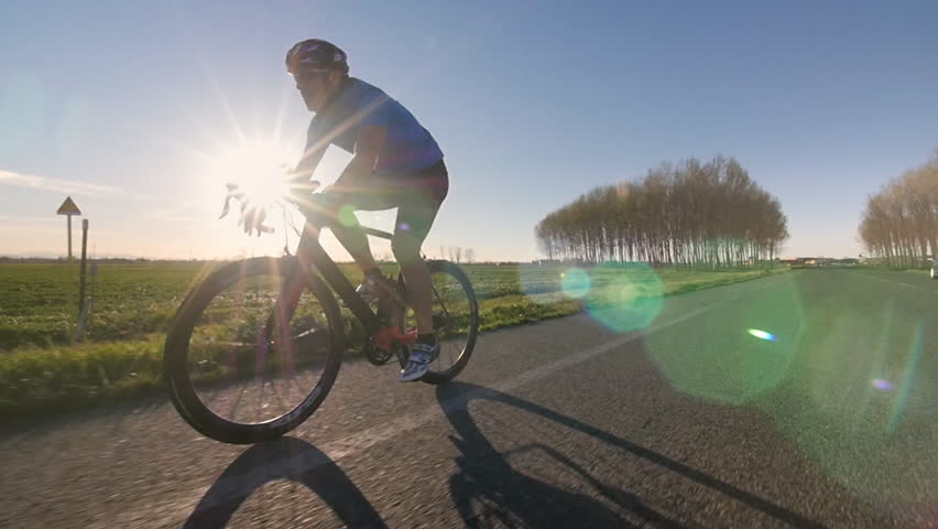 healthy man riding bike working out. training fitness outdoors. tracking shot from camera car slowmotion #9521552