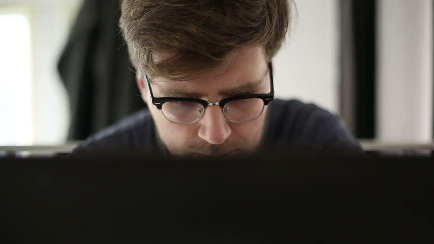 Intelligent man wearing spectacles works at the computer in studio | Shutterstock HD Video #9525092