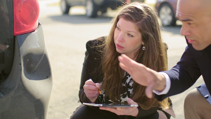 Female insurance agent inspects damage to a man's car and makes notes on a tablet computer, during discussion with man.  Recorded in 4K and cropped.