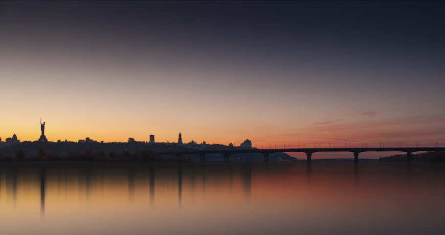 Time lapse footage of Kiev Pechersk Lavra, Patona Bridge on the Dnieper river, Mother Motherland, lights of urban Kiev at evening. Ukraine, Eastern Europe, romantic.