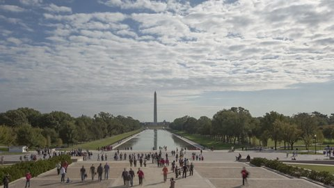 WASHINGTON D.C., USA - OCT 14, 2012: 4K time lapse crowd of people walking around at Washington Monument view from Lincoln Memorial with dark cloudes in the sky