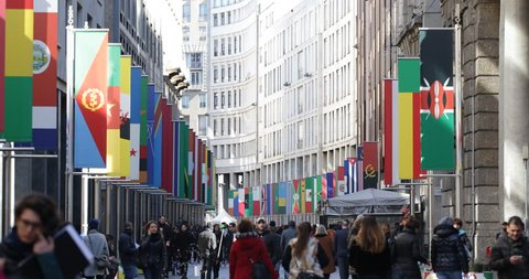 MILAN, ITALY - MARCH 8, 2015 Milan Shopping Street Pedestrians Walk Busy City Expo 2015 International Flags ( Ultra High Definition, UltraHD, Ultra HD, UHD, 4K, 2160P, 4096x2160 )