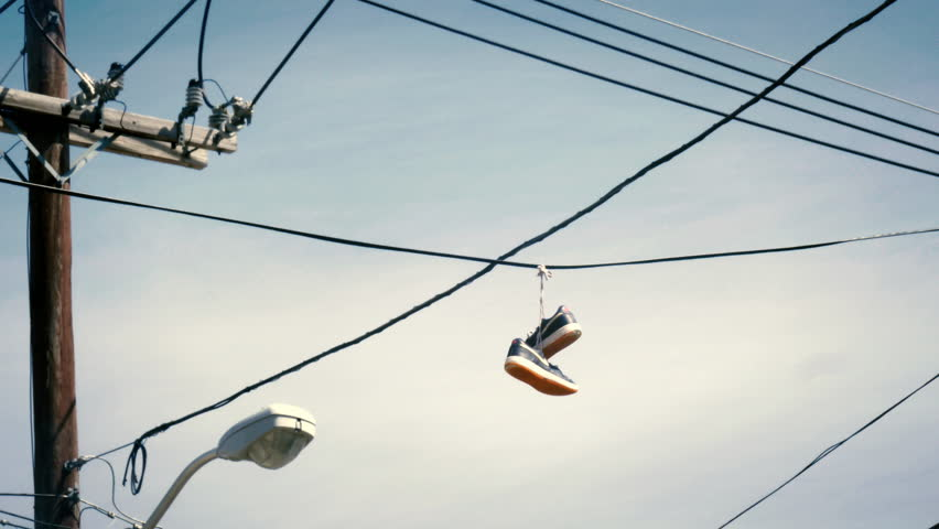 Hanging Pictures On Wire sneakers hanging from telephone wire in a bad neighborhood is a