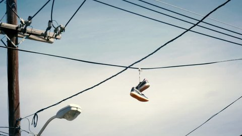 Sneakers hanging from telephone wire in a bad neighborhood is a symbol for a drug dealer
