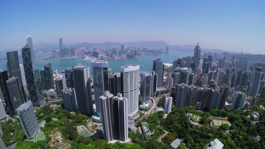 Hong Kong City Aerial Track Shot. Beautiful Clear Blue Sky. 4K Aerial view capturing the general Hong Kong and Kowloon Island. Left movement wide track shot.