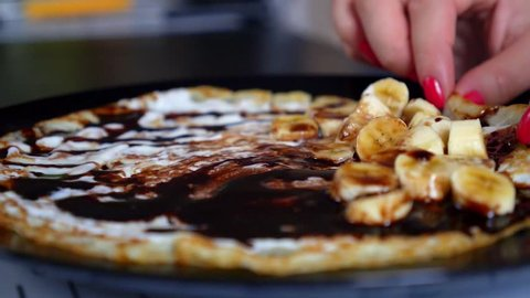 Close-up Wrapping Chocolate Crepes with Sauce and Bananas on the Plate. HD, 1920x1080.