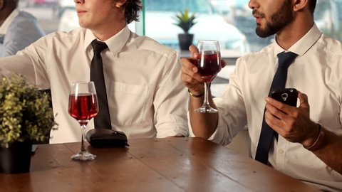 Waiter in a restaurant brings bill to table for after work drinks, work colleague then calculate bill with smart phone.