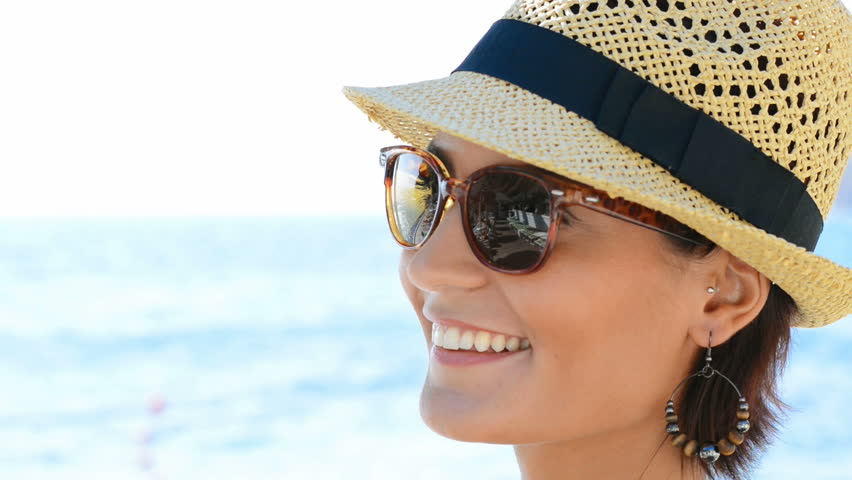 a2d970881d Portrait Of Smiling Young Woman Wearing Sunglasses and straw hat in front  of the sea. Happy carefree girl laughing at the beach in summer.