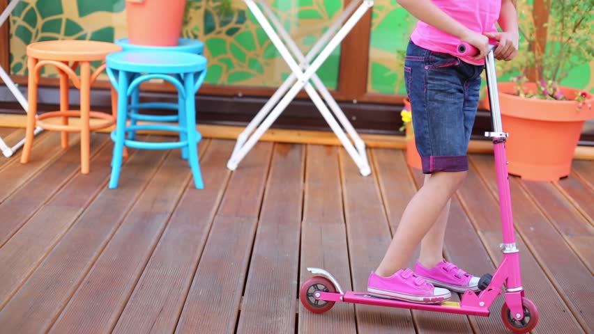 Legs of little girl on scooter on floor in cafe at summer | Shutterstock HD Video #9718142