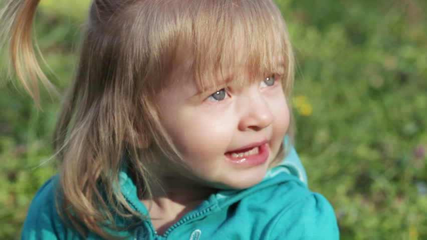 Little girl child sneezes in nature and expresses emotions