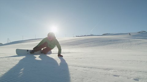 CLOSE UP: Snowboarder carving on groomed snow in ski resort