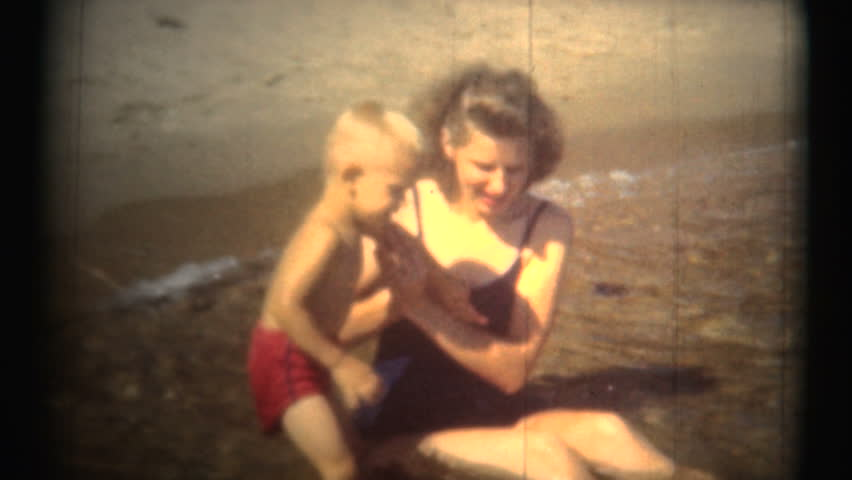 LOS ANGELES, USA - JULY 1953: Mom and Toddler Having Fun At Beach. A great shot of a mom playing with her sun at the beach.