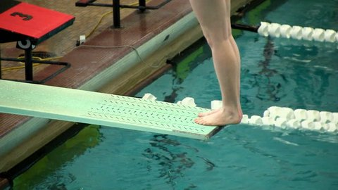 High school female diver stands at the edge of a diving board and springs herself off into a back dive during diving meet
