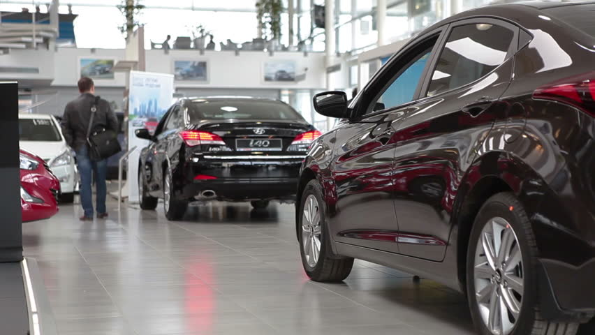 ST. PETERSBURG, RUSSIA - CIRCA APR, 2015: Customers look at vehicles standing in car dealership showroom. The Rolf Lahta is a official dealer of Hyundai | Shutterstock HD Video #9769862