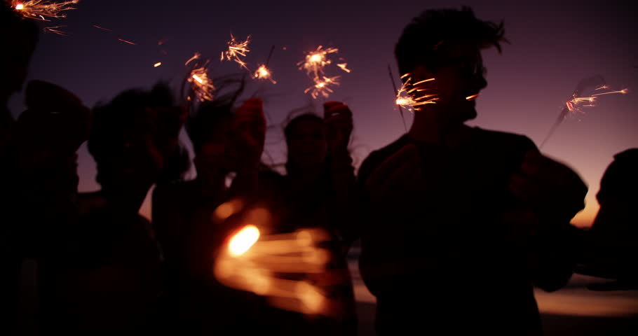 Group of friends having a beachparty together and celebrating with sparklers in the twilight in Slow Motion
