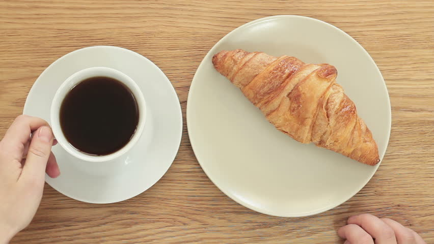 Overhead view of a woman hand with a cup of black coffee and a freshly baked croissant, top view  #9780719