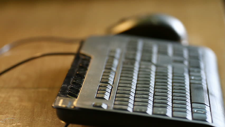 Typing and moving mouse closeup with shallow depth of field over a wood table