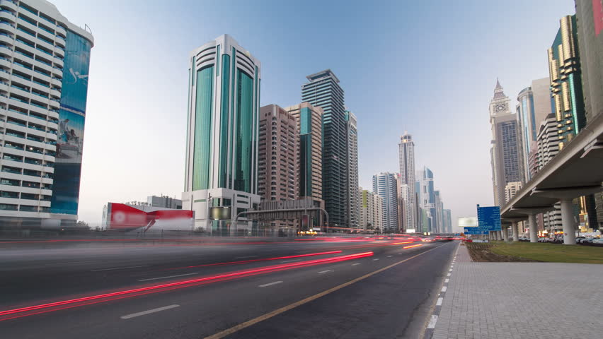 Skyscrapers at the Sheikh Zayed Road from day to night transition with traffic and lighhs torn on in Dubai timelapse hyperlapse at twilight 4K