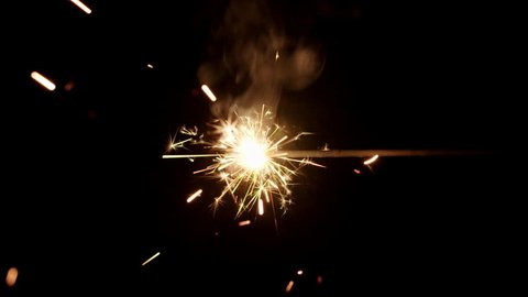 Sparkler burning from left to right in center of black background.  Recorded in 4K at 60fps.