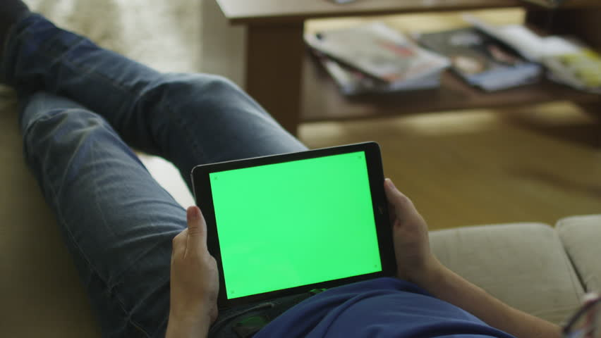 Man is Laying on Couch at Home and Watch on Tablet with Green Screen in Landscape Mode. Shot on RED Cinema Camera in 4K (UHD). | Shutterstock HD Video #9813032