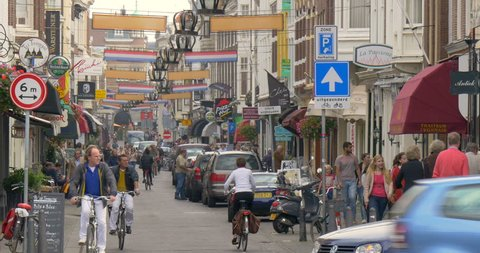 Hague North Holland Netherlands Europe 13 SEP 2014: Den Haag city shopping street with walking people, tourists, cycling bicycles, old dutch architecture buildings, travel, european urban tourism view