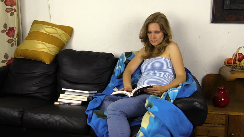 Pregnant woman read book on sofa and caress her stomach belly. Shot on Canon XA25