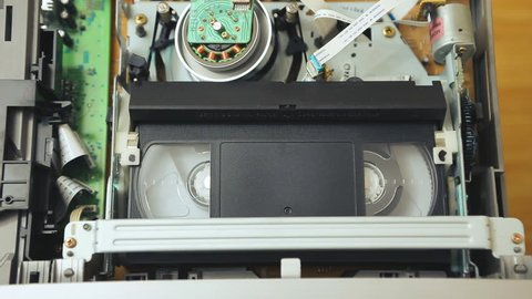 playback of videotape in the VCR Videorecorder S-VHS, VHS. The sequence of video footage. magnetic videotape in the VCR mechanism. Videorecorder S-VHS, VHS