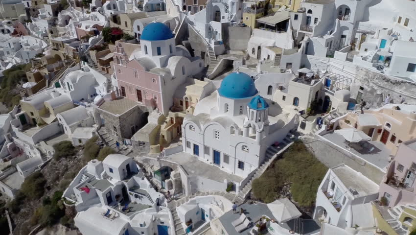 Tilt up Aerial Shot of Greek Santorini Island with Blue Dome Churches in Oia. | Shutterstock HD Video #9877352