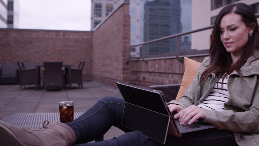 Panning view of woman relaxing on roof top using laptop. | Shutterstock HD Video #9888512