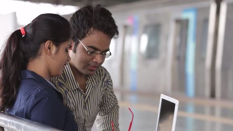 Young office going Indian man and woman working on lap top on metro station.