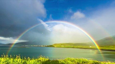 Iceland - 15 June 2015: Grass moving in the breeze and rainbow in Neighborhoods Grundarfjordur (Grundarfjörður) - a favorite place for nesting birds. 4K TimeLapse