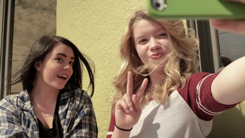 Two Teens Sit Outside A Coffee Shop And Take Fun Selfies Together (4K)