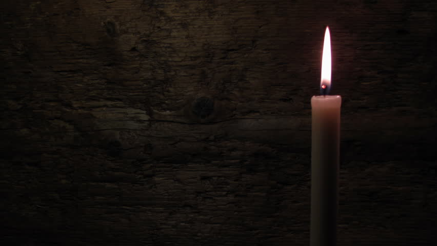 Candle on a wooden background. Fire deflected from the draft.