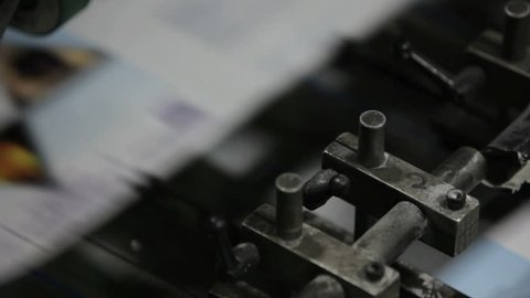 A professional printing press in action, churning out a magazine.