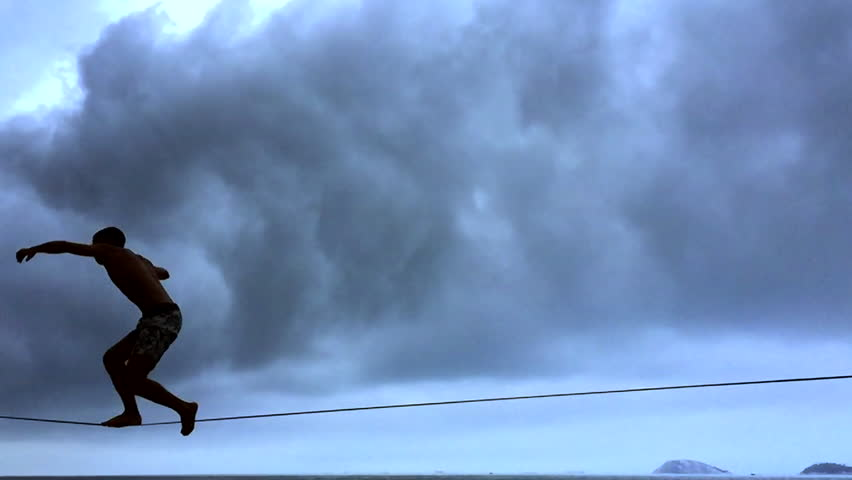Silhouette of person on slackline in slow motion against cloudy skies in Rio de Janeiro Brazil