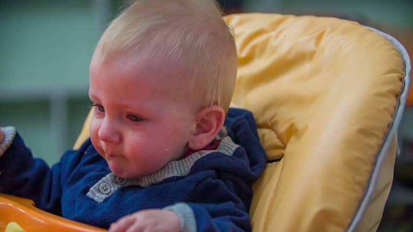 Crying Baby Seating In The Eating Chair. Young Baby Boy Seating In ...